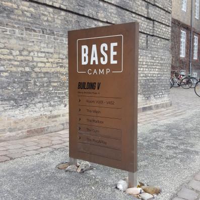 Henvisningsskilt i rå kobberplade med serigrafitryk til Base Camp.
