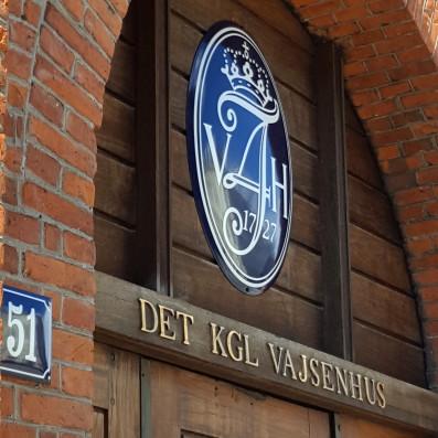 Ovalt emaljeskilt monteret over port til Det Kgl. Vajsenhus samt husnummer på murstensvæg.
