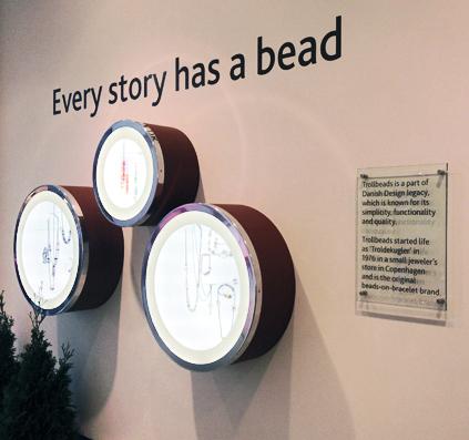 troldekugler butik glasskilt med historie i sorte foliebogstaver og sandblæst folie på bagsiden samt folie tekst monteret på væg