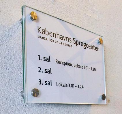 glaskilt med folieprint monteret på væg hos københavns sprogcenter skilt af skiltefabrikken københavn østerbro