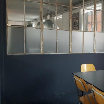 Sandblæst folie opsat imellem møderum og kontor.