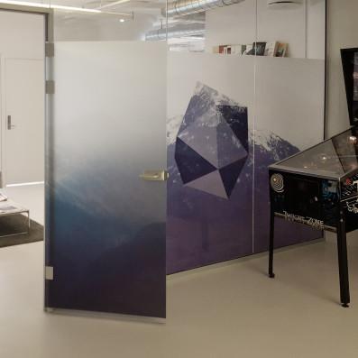 Printet sandblæst folie opsat på glasvægge i kontormiljø.