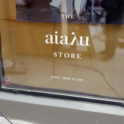 Lille tekst i folie på butiksvindue. Aiayu Store.