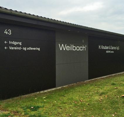 folietekster monteret på facade mur af skiltefabrikken weilbach samt h knudsen og sønner københavn østerbro hvid indgang vareindlevering vareudlevering hus nr 43 generatorvej herlev